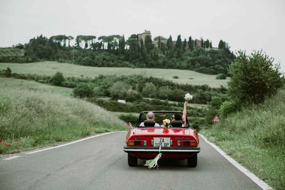 Just married couple driving in a red cabriolet in Italy